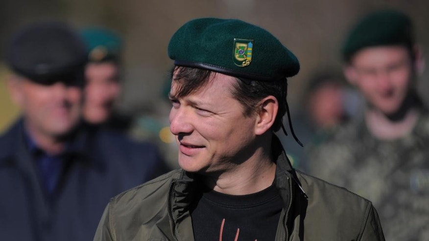 FILE In this photo taken on Saturday, April  5, 2014, Oleh Lyashko, center, leader of Ukrainian Radical Party and presidential candidate who supported the protests that ousted Russian-leaning president Viktor Yanukovych and his government walks during his visit to Ukrainian troops at their camp near Ukraine-Russian border outside Chernihiv, 140km (87 miles) northeast of Kiev, Ukraine. Once, he was little more than an entertaining curiosity in Ukraine?s politics, noted for bringing vegetables and livestock to parliament where he was the only representative of a fringe nationalist party. But after Oleh Lyashko took up arms in Ukraine's east and interrorgated near-naked detained separatists, his star rose.(AP Photo/Osman Karimov, file)
