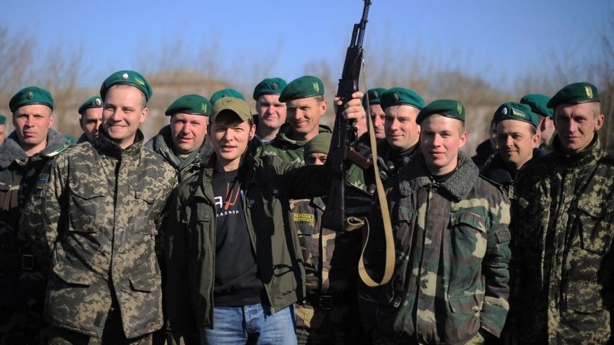 FILE In this photo taken on Saturday, April  5, 2014, Oleh Lyashko, center left, leader of Ukrainian Radical Party and presidential candidate who supported the protests that ousted Russian-leaning president Viktor Yanukovych, poses with Ukrainian soldiers and officers at their camp near Ukraine-Russian border outside Chernihiv, 140km (87 miles) northeast of Kiev, Ukraine. Once, he was little more than an entertaining curiosity in Ukraine?s politics, noted for bringing vegetables and livestock to parliament where he was the only representative of a fringe nationalist party. But after Oleh Lyashko took up arms in Ukraine's east and interrorgated near-naked detained separatists, his star rose. (AP Photo/Osman Karimov, file)