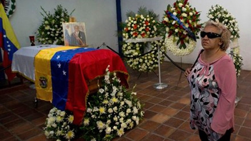 A woman stands near the coffin that contain the remains of Venezuela's late President Jaime Lusinchi during a memorial service in Caracas, Venezuela, Thursday, May 22, 2014. The former president, who struggled to tame an economic crisis sparked by plunging oil prices in the late 1980s and then saw his reputation tarnished by allegations of corruption after leaving office, died Wednesday, May 21, 2014. He was 89. (AP Photo/Fernando Llano)