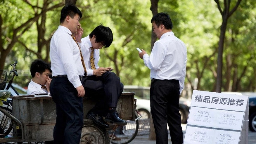 In this Saturday, June 7, 2014 photo, real estate sales agents look at their smartphones near a display board showing properties for sale and for rent, as they wait for potential buyers in Beijing. China's house prices have marched higher for 15 years, helping to drive an economic boom but making home ownership unaffordable for many families. Now the slump is dragging down economic growth that already was slowing. Some analysts worry banks might be shaken if developers default on loans. (AP Photo/Andy Wong)