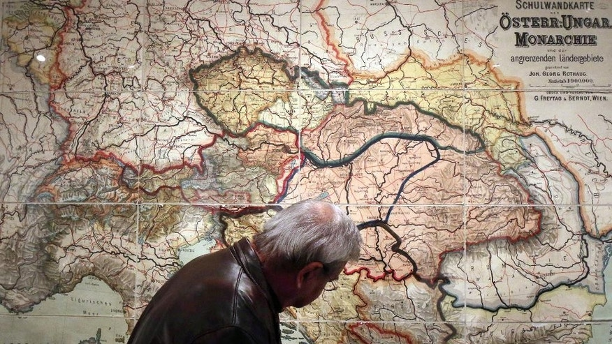 ADVANCE FOR SUNDAY JUNE 15 2014 TO  GO WITH STORY WWI-THE GREAT WAR -In this Tuesday, April 1, 2014 photo, a visitor looks at a school wall map of the Austrian-Hungarian Empire from 1900 that was corrected with new borders after World War I at a special exhibition on World War I at the Schallaburg castle, in Austria. (AP Photo/Ronald Zak)