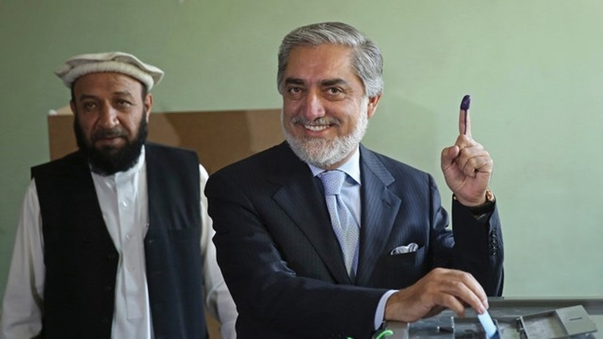 June 14, 2014: Afghanistan's presidential candidate Abdullah Abdullah, right, poses for photos before he casts his vote as his first vice president candidate, Mahoammad Khan, left, waits at a pooling station in Kabul, Afghanistan.