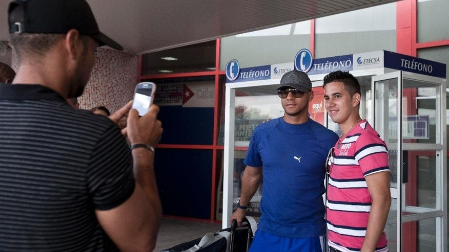 "In this May 29, 2014 photo, Yulieski Gourriel, center, a player with Cuba's baseball team Industriales, poses for a photo with a fan before catching his flight at the Jose Marti International Airport, in Havana, Cuba. Gourriel signed a contract with the DeNA BayStars of Yokohama, Japan for the next half-year. ""For me it's a dream come true to play professional baseball in Japan, the second-best (league) in the world after the United States,"" Gourriel said. (AP Photo/Franklin Reyes)"