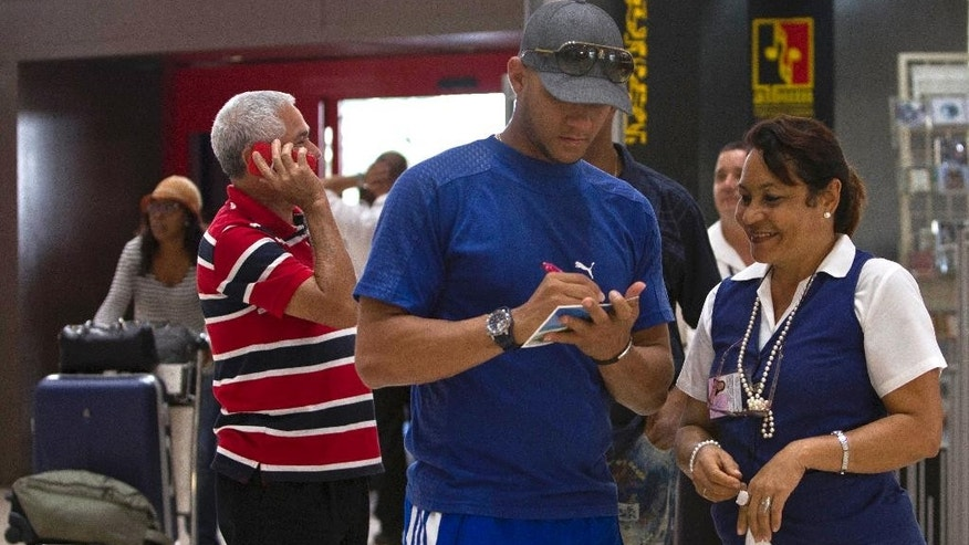 In this May 29, 2014 photo, Yulieski Gourriel, former player with the Cuban baseball team Industriales, autographs a postcard for airport worker Marbelis Pompa before catching his flight at the Jose Marti International Airport in Havana, Cuba. Travelers and airport workers approached to ask for autographs and have their picture taken with one of Cuba's biggest baseball stars as he readied for a transoceanic flight to join his new team: the DeNA BayStars of Yokohama, Japan. (AP Photo/Franklin Reyes)