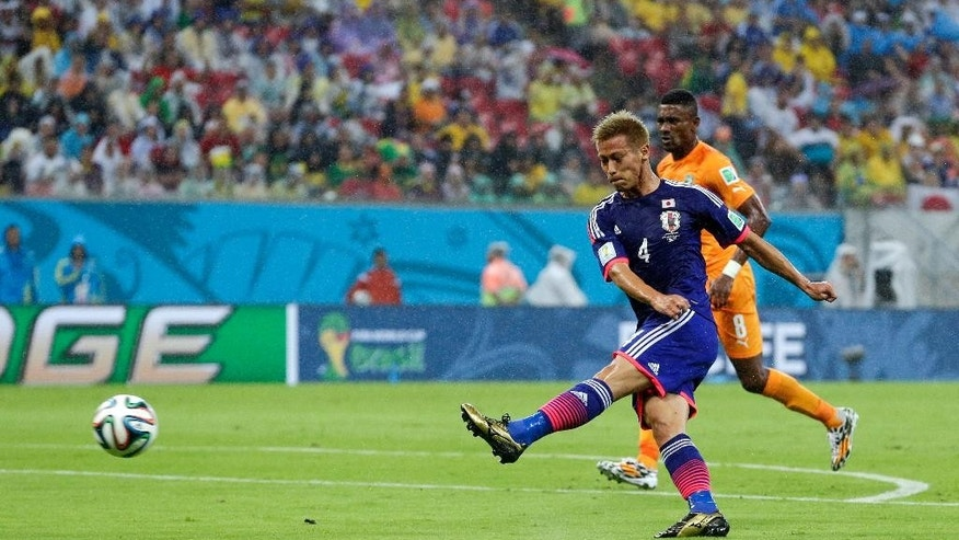 Japan's Keisuke Honda (4) scores his side's first goal ahead of Ivory Coast's Salomon Kalou (8) during their group C World Cup soccer match at the Arena Pernambuco in Recife, Brazil, Saturday, June 14, 2014. (AP Photo/Petr David Josek)