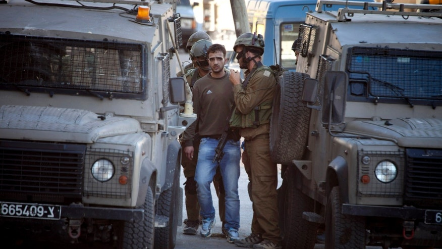 June 14, 2014: Israeli soldiers arrest a Palestinian man in the West Bank City of Hebron.