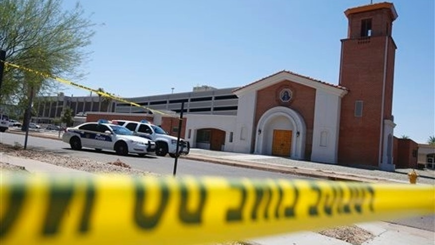 Phoenix police were still on the scene after a Wednesday evening attack left a priest shot and killed and another injured at the Roman Catholic church the Mother of Mercy Mission on Thursday, June 12, 2014, in Phoenix.  Police have no suspects at this point, but they are canvassing the neighborhood and going over physical evidence from the scene. (AP Photo/Ross D. Franklin)