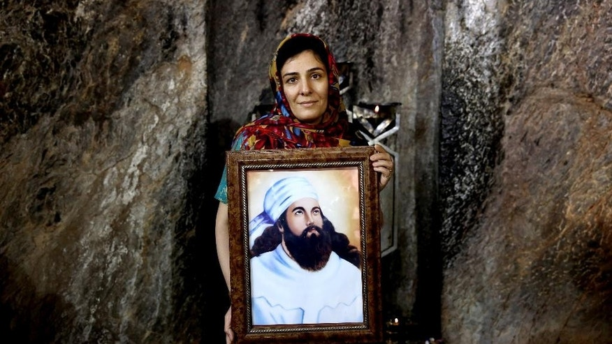 In this Friday, June 13, 2014 photo, a Zoroastrian woman holds a portrait of  prophet Zoroaster in Chak Chak, a mountain shrine, some 600 kilometers (370 miles) southeast of the capital Tehran, Iran. Zoroastrianism is a monotheistic religion predating Christianity, Islam and Judaism, founded some 3,800 years ago by the prophet Zoroaster. It was the dominant religion in Persia before the Arab conquest. (AP Photo/Ebrahim Noroozi)