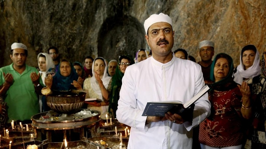 In this Friday, June 13, 2014 photo, Zoroastrian priest Kamran Lorian leads a prayer in Chak Chak, a mountain shrine, some 600 kilometers (370 miles) southeast of the capital Tehran, Iran. Adherents of the Zoroastrian religion from around the world gathered at a mountain shrine in central Iran this week to celebrate their Persian roots, praying in remembrance of a princess who fled the 7th century Arab invasion. (AP Photo/Ebrahim Noroozi)