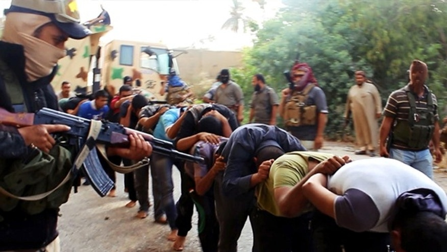 June 14, 2014: This image posted on a militant website which has been verified and is consistent with other AP reporting, appears to show militants from the Al Qaeda-inspired Islamic State of Iraq and the Levant (ISIS) leading away captured Iraqi soldiers dressed in plain clothes after taking over a base in Tikrit, Iraq.