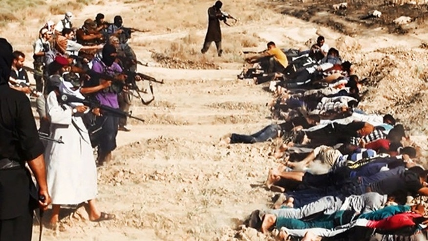 June 14, 2014: This image posted on a militant website which has been verified and is consistent with other AP reporting, appears to show militants from the Al Qaeda-inspired Islamic State of Iraq and the Levant (ISIS) taking aim at captured Iraqi soldiers wearing plain clothes after taking over a base in Tikrit, Iraq.