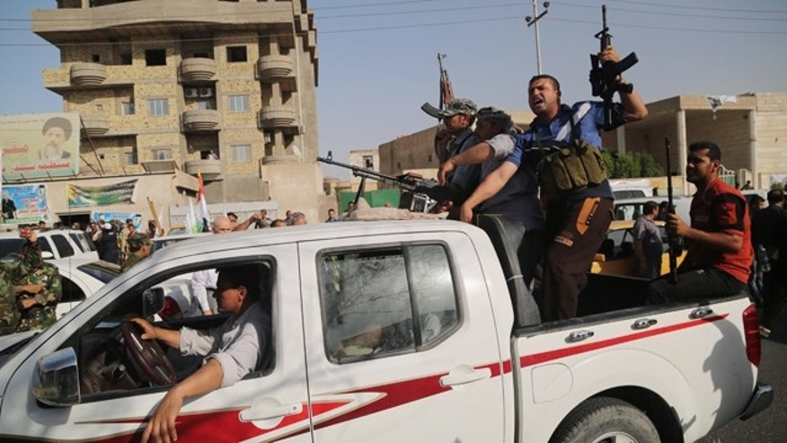June 14, 2014: Iraqi Shiite fighters deploy with their weapons in Basra, 340 miles southeast of Baghdad. (AP Photo/ Nabil Al-Jurani)