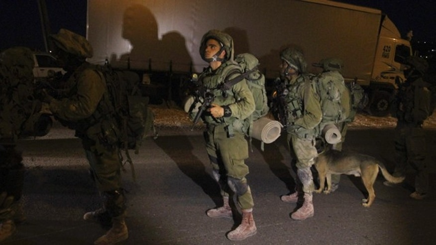 June 15, 2014: Israeli soldiers patrol during a military operation to search for three missing teenagers near the West Bank city of Hebron. (AP Photo/Nasser Shiyoukhi)