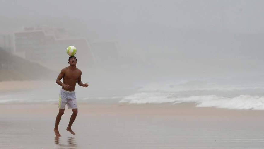 A man heads a soccer ball during a stroll along the beach on a rainy day in Natal, Brazil, Saturday, June 14, 2014. Natal is one of 12 cities hosting games during the 2014 World Cup soccer tournament. (AP Photo/Julio Cortez)