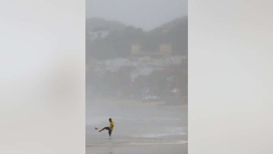 Arthur Gomes Freire, 28, kicks a ball during a rainy day at the beach in Natal, Brazil, Saturday, June 14, 2014. Natal is one of 12 cities hosting games during the 2014 World Cup soccer tournament. (AP Photo/Julio Cortez)