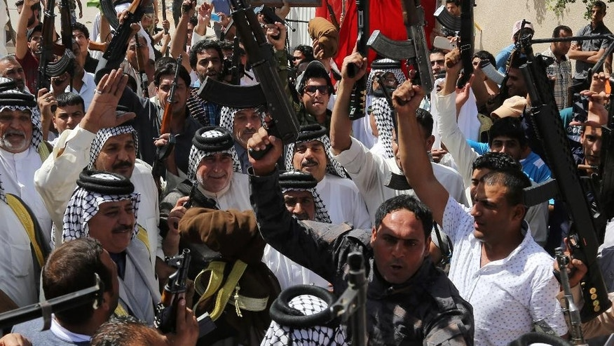 In this Saturday, June 14, 2014 photo, Iraqi Shiite tribal fighters raise their weapons and chant slogans against the al-Qaida-inspired Islamic State of Iraq and the Levant (ISIL) in Baghdad's Sadr city, Iraq. Emboldened by a call to arms by the top Shiite cleric, Iranian-backed militias have moved quickly to the center of Iraq's political landscape, spearheading what its Shiite majority sees as a fight for survival against Sunni militants who control of large swaths of territory north of Baghdad. The poster at top depicts Grand Ayatollah Mohammed Sadiq al-Sadr, the late father of Shiite cleric Muqtada al-Sadr. (AP Photo/ Karim Kadim)