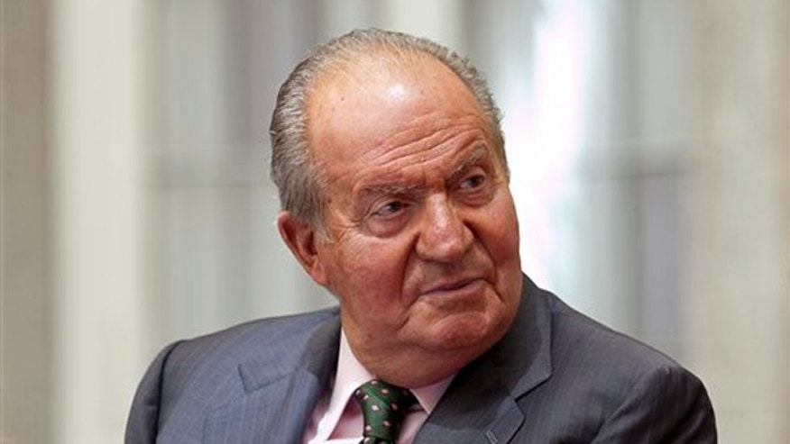 FILE- In this Friday, June 13, 2014 file photo, King Juan Carlos of Spain attends to commemorating the 25th anniversary of SECOT at El Pardo Palace in Madrid, Spain. Spain is preparing a form of legal indemnity to cover King Juan Carlos once he abdicates the throne in favor of his son. When 46-year-old Prince Felipe takes over as head of state on Thursday _ he will become Felipe VI _ the 76-year-old Juan Carlos will lose the legal cover he has enjoyed since becoming king in 1975. Deputy Prime Minister Soraya Saenz de Santamaria says the new indemnity should shield Juan Carlos, who in retirement retains his title of king, from legal probes. Any possible legal case involving him would be examined by the Supreme Court, which has a much higher threshold for evidence. (AP Photo/Abraham Caro Marin, file)
