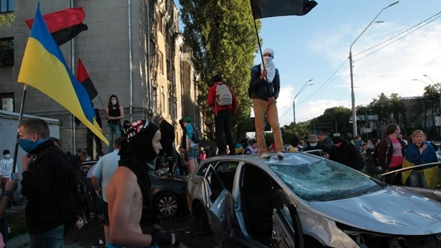 June 14, 2014: Ukrainian protesters destroy cars near the Russian Embassy during a rally in Kiev. About a hundred protesters hurled eggs and paint at the embassy and overturned several parked cars with diplomatic plates. (AP Photo/Sergei Chuzavkov)