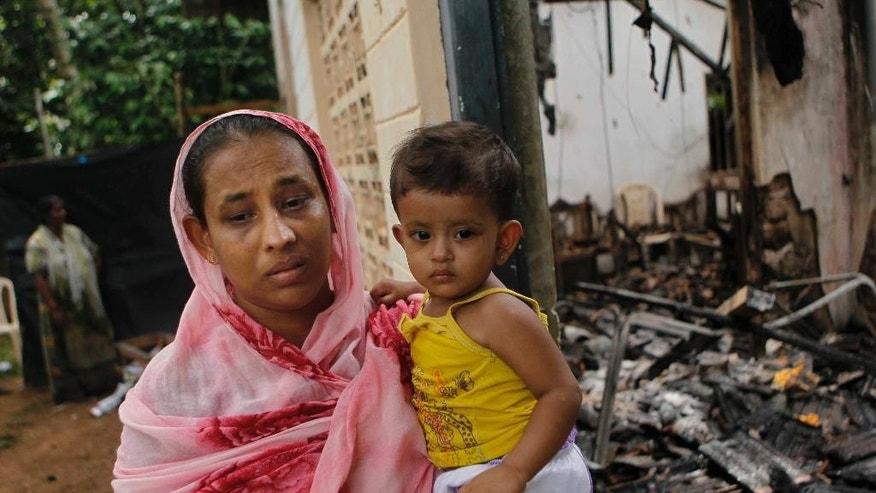 A Sri Lankan Muslim woman carries her daughter while standing outside her burnt house in Adhikarigoda , a village near Aluthgama town, 50 kilometers (31.25 miles) south of Colombo, Sri Lanka, Monday, June 16, 2014. At least three Muslims were killed after a right-wing Buddhist group with alleged state backing clashed with Muslims in southwestern Sri Lanka, a government minister said Monday. Dozens of shops were burned, homes looted and some mosques attacked in the violence Sunday night in the town of Aluthgama, local residents said. (AP Photo/Eranga Jayawardena)