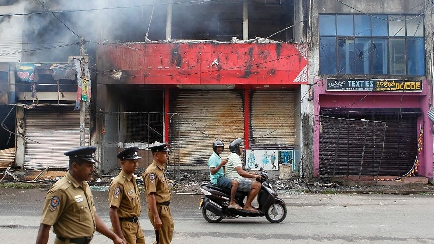 Sri Lankan police officers walk past a burnt shop in Aluthgama, town, 50 kilometers (31.25 miles) south of Colombo, Sri Lanka, Monday, June 16, 2014. At least three Muslims were killed after a right-wing Buddhist group with alleged state backing clashed with Muslims in southwestern Sri Lanka, a government minister said Monday. Dozens of shops were burned, homes looted and some mosques attacked in the violence Sunday night in the town of Aluthgama, local residents said. (AP Photo/Eranga Jayawardena)