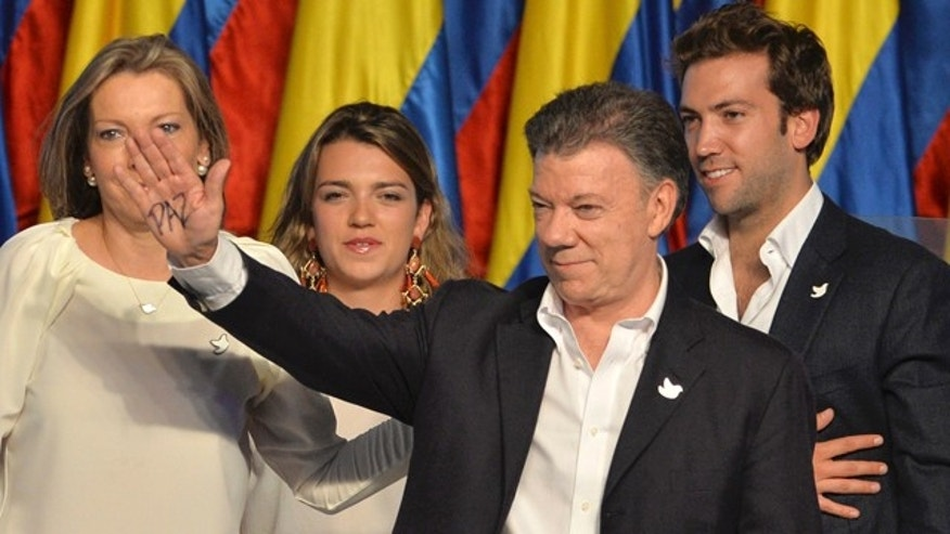 June 15, 2014: With the word 'peace' written on his hand, President Juan Manuel Santos waves during his victory rally next to first lady Maria Clemencia Rogriguez, left, his daughter Maria Antonia Santos and son Martin Santos at his campaign headquarters in Bogota, Colombia. (AP Photo/Santiago Cortez)