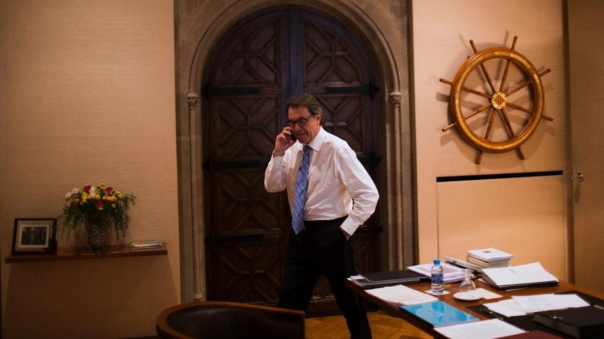 In this photo taken on Friday, June 13, 2014 Catalonia's regional president Artur Mas talks on his phone ahead of an interview inside the Generalitat Palace, the main head office of the Government of Catalonia,  in Barcelona, Spain. If Catalonia's regional president wins backing for his goal in a planned Nov. 9 local referendum on whether to secede, his success will not only fuel the independence cause in the nearby Basque country. It will also encourage other separatist-minded regions across the continent, such as Belgium's Dutch speakers, even if Scotland votes against its own proposal for independence in September. (AP Photo/Emilio Morenatti)