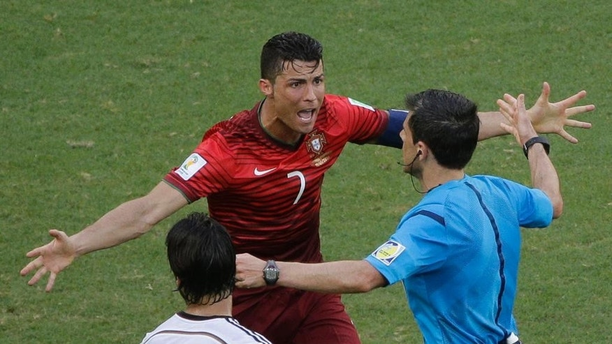 Portugal's Cristiano Ronaldo protests to referee Milorad Mazic from Serbia during the group G World Cup soccer match between Germany and Portugal at the Arena Fonte Nova in Salvador, Brazil, Monday, June 16, 2014. (AP Photo/Christophe Ena)