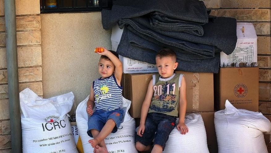 In this Sunday, June 15, 2014 photo, Iraqi children sit atop bags of rice donated by the International Committee for  the Red Cross, in Alqosh, a village of some 6,000 inhabitants about 50 kilometers (31 miles) north of Mosul, northern Iraq. Dozens of Christian families that fled to this ancient Iraqi village have taken a much-traversed route -- many from their minority community have escaped to Alqosh before, in fear for their lives. This time, few say they want to go back to their homes, seeking safety under the Kurdish forces known as the peshmerga. (AP Photo)