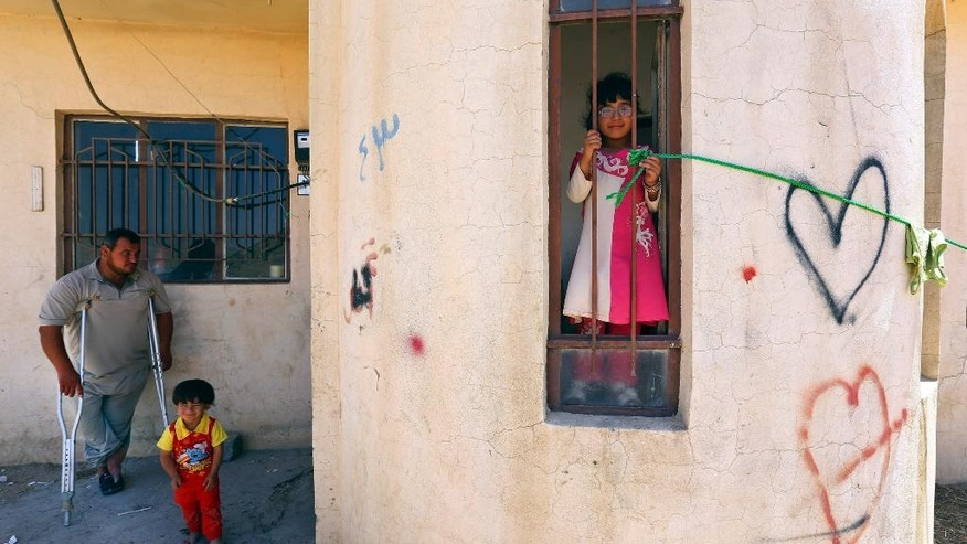 In this Sunday, June 15, 2014 photo, an Iraqi family poses for a picture in Alqosh, a village of some 6,000 inhabitants about 50 kilometers (31 miles) north of Mosul, northern Iraq. Dozens of Christian families that fled to this ancient Iraqi village have taken a much-traversed route -- many from their minority community have escaped to Alqosh before, in fear for their lives. This time, few say they want to go back to their homes, seeking safety under the Kurdish forces known as the peshmerga. (AP Photo)