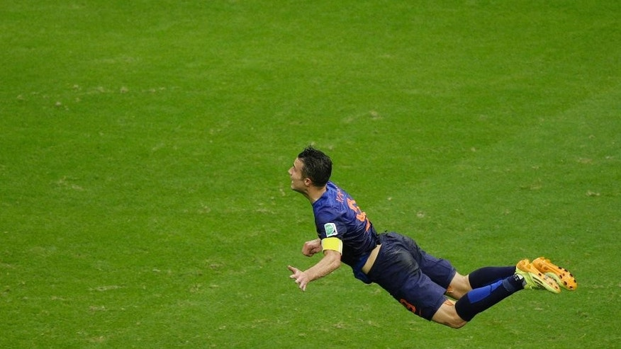 In this Friday, June 13, 2014 photo, Netherlands' Robin van Persie heads the ball to score during the group B World Cup soccer match between Spain and the Netherlands at the Arena Ponte Nova in Salvador, Brazil. The Dutchman's header that looped over a stranded Iker Casillas in the Spain goal was not only very special but historic. By taking his tally to 45 goals for his country, the Manchester United forward also became the first Dutch player to score in three consecutive World Cups.(AP Photo/Christophe Ena)
