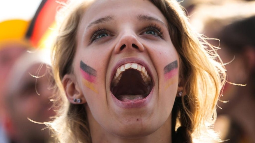 A German soccer fan celebrates their team's third goal during their first game at the World Cup 2014 at a public viewing zone called 'fan mile' in Berlin, Monday, June 16, 2014. Germany plays against Portugal in group G match at the soccer World Cup 2014 in Brazil. (AP Photo/Markus Schreiber)