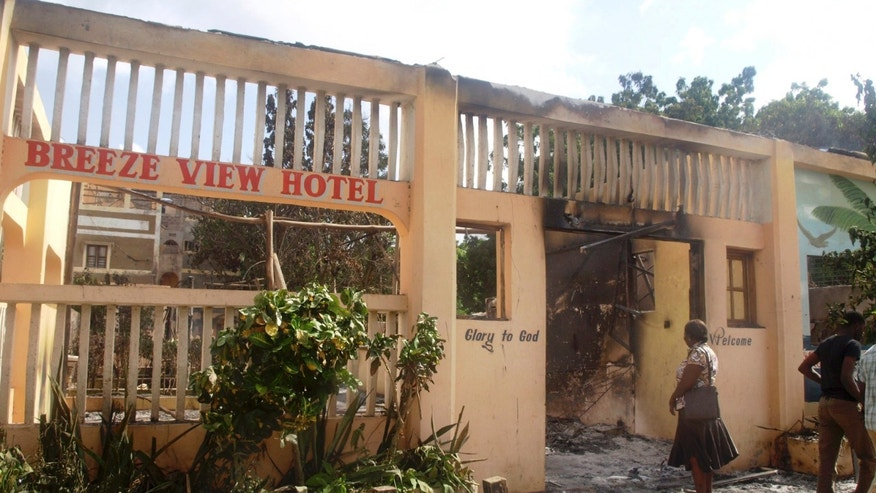 June 16, 2014 - A woman observes the remains of the Breeze View Hotel,attacked by militants in the town of Mpeketoni, 60 miles from the Somali border in Kenya. Somali extremists wielding automatic weapons attacked the small Kenyan coastal town for hours, assaulting the police station, setting two hotels on fire, and spraying bullets into the street killing dozens, officials said.