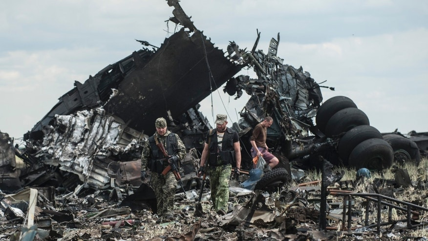 June 14, 2014 - Pro-Russian fighters collect ammunition from the site of remnants of a downed Ukrainian army aircraft Il-76 at the airport near Luhansk, Ukraine. Separatists shot down the military transport plane in the country's restive east, killing all 49 service personnel on board, Ukrainian officials said.