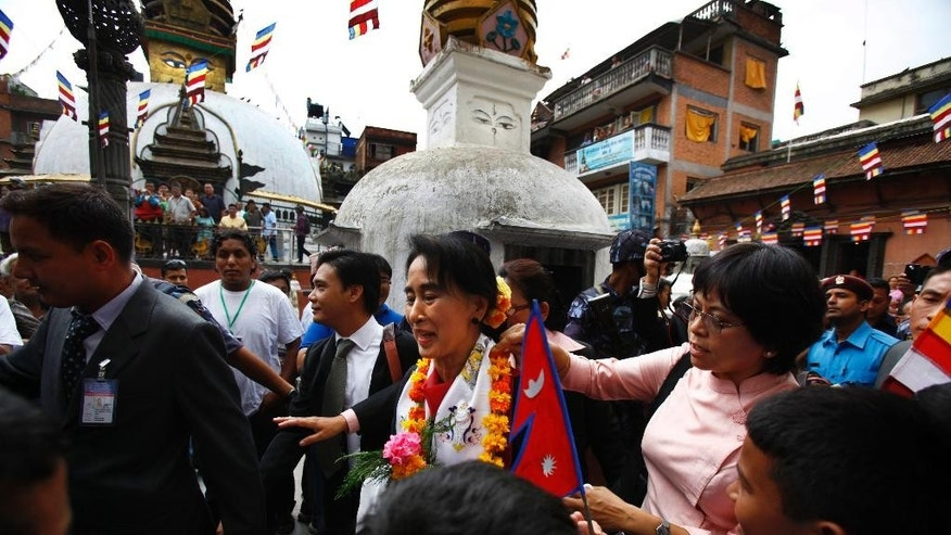 Nepalese people welcome Myanmar opposition leader Aung San Suu Kyi upon arrival at Sigal Monastery in Katmandu, Nepal, Monday, June 16, 2014. Suu Kyi arrived in Nepal Friday to attend a democracy conference, meet top political leaders and visit Buddhist pilgrimage sites. (AP Photo/Niranjan Shrestha)