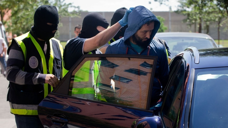Spanish police officers arrest a man suspected of belonging to an Jihadist recruiting network on June 16, 2014.