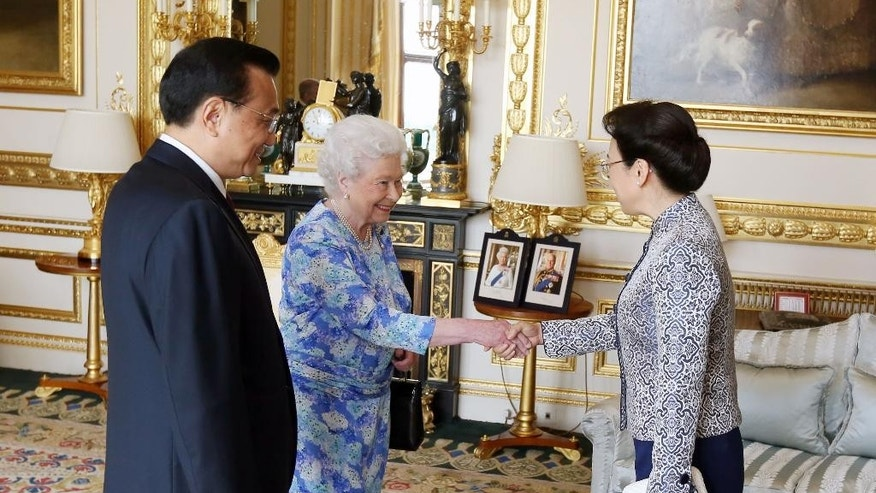 Britain's Queen Elizabeth II, center, receives Chinese premier Li Keqiang, left, and his wife Cheng Hong at Windsor Castle, during their visit to the Britain, Tuesday, June 17, 2014. (AP Photo/Steve Parsons, pool)