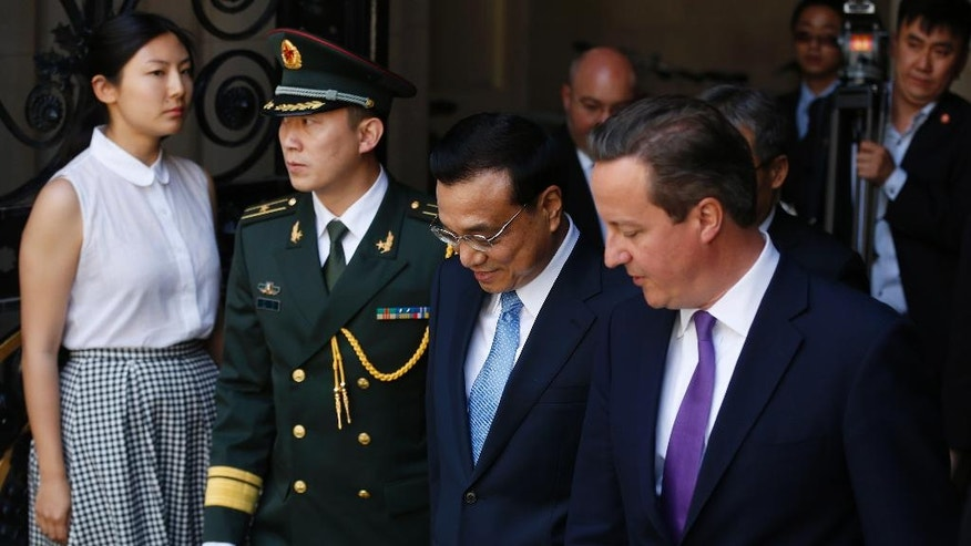 Chinese Premier Li Keqiang, second right, arrives with British Prime Minister David Cameron, right, for a meeting at 10 Downing Street in London, Tuesday, June 17, 2014. The Chinese leader met with Prime Minister David Cameron and other senior government officials, and the two sides are expected to announce a slew of trade and investment deals. (AP Photo/Sang Tan)