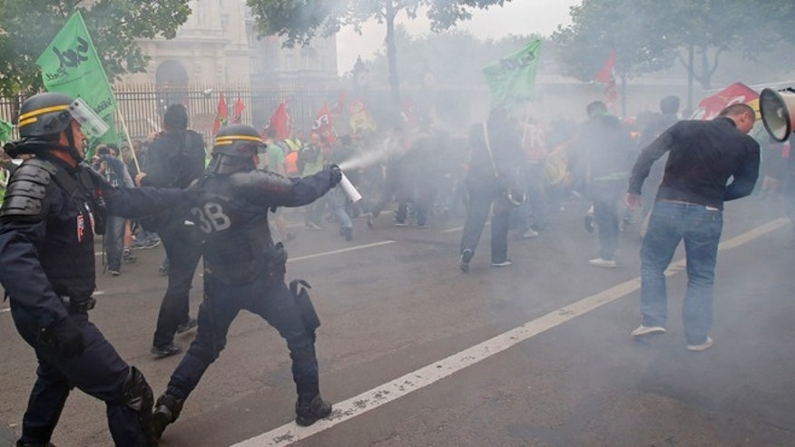 June 17, 2014: French riot police fire tear gas at striking train workers during a protest over a bill to reform the state-run railway system in Paris. A weeklong strike by rail workers has caused one of the worst disruptions to the countrys rail network in years and is heating up as the reform bill goes to the lower house of Parliament for debate Tuesday. France's Foreign ministry is in the background.