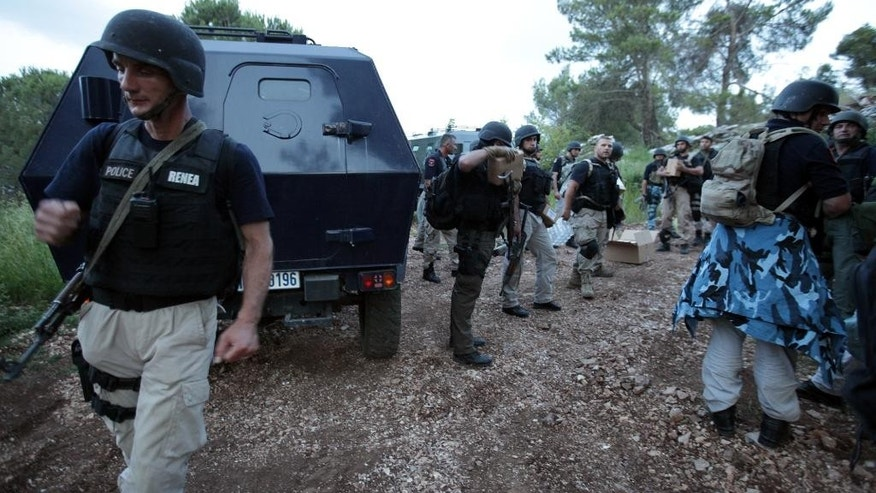 Albanian special forces police surround the marijuana-growing village of Lazarat, south of the capital Tirana, Monday June 16, 2014. Gangs based in Lazarat are believed to produce about 900 metric tons of cannabis a year, worth about 4.5 billion euros ($6.1 billion) _ roughly half the small Balkan country's GDP. (AP Photo/Hektor Pustina)