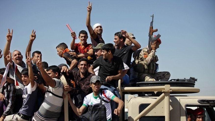 June 17, 2014: Iraqi men flash victory signs as they leave the main recruiting center to join the Iraqi army in Baghdad, Iraq, after authorities urged Iraqis to help battle insurgents. (AP)