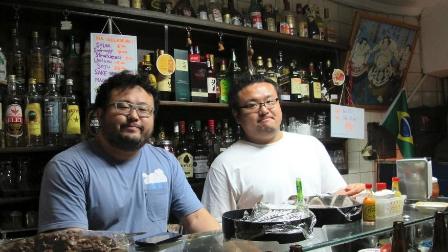 "In this June 10, 2014 photo,  William Takahiro Higuchi, left, and Wagner Yoshihiro Higuchi tend the Bar Kintaro, in Asian-flavored Libertade district of Sao Paulo, Brazil. Brazil hosts the world's largest ethnic Japanese population outside Japan -1.5 million, or half of the roughly 3 million scattered around the globe.  Many ""Nikkei"" like the Higuchi brothers have forged vibrant hybrid identities where sumo meets samba.  (AP Photo/Joji Sakurai)"