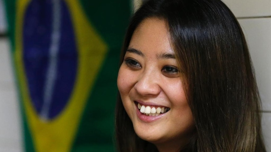 In this June 10, 2014, photo, Sao Paulo's former Miss Okinawa, Lais Miwa Higa, speaks during an interview at Bar Kintaro in Sao Paulo, Brazil. The elite Sao Paulo University Master's degree student in anthropology, who is considering a PhD, has trouble being perceived among Brazilian peers as more than a Japanese geisha doll. (AP Photo/Shuji Kajiyama)