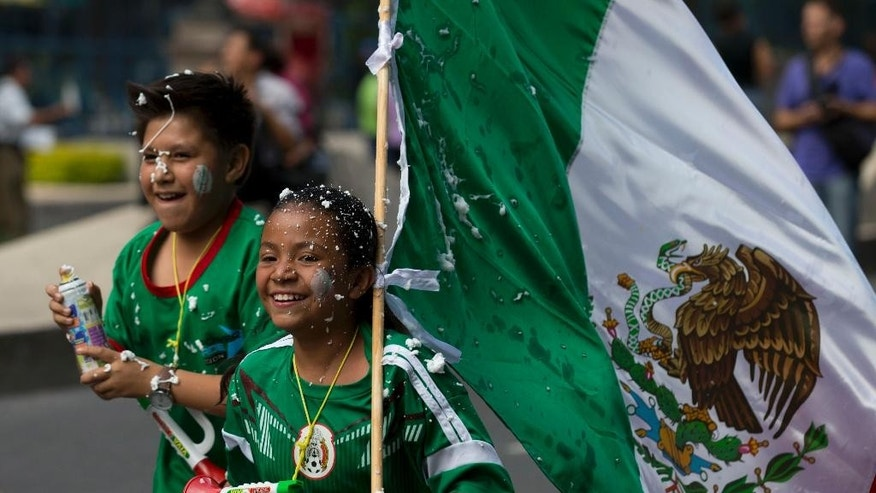 A couople of children, fans of the Mexican national soccer team, celebrate by the Independence Monument after their team tied with Brazil in their 2014 World Cup soccer match, in Mexico City, Tuesday, June 17, 2014. Mexico claimed a deserved point against Brazil in a largely frustrating Group A game which finished 0-0 at Estadio Castelao in Fortaleza, Brazil. (AP Photo/Rebecca Blackwell)