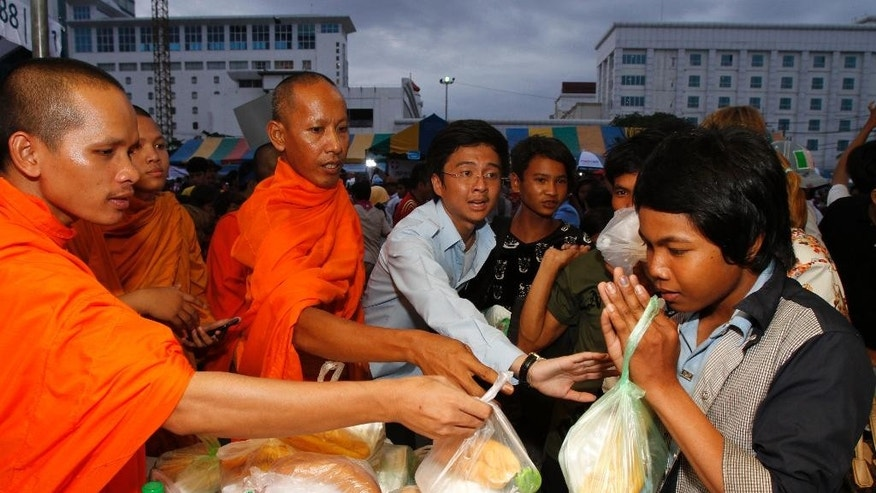 Cambodian Buddhist monks give donated dinner to migrant workers on their arrival from Thailand at a Cambodia-Thai's international border gate in Poipet, Cambodia, Tuesday, June 17, 2014. The number of Cambodians who have returned home from Thailand this month after a threatened crackdown on foreigners working illegally has topped 160,000, a Cambodian official said Monday. Thai officials insist the cross-border movement is voluntary and is not forced repatriation. They say Thai military and government resources were used to transport workers who decided to return home after being laid off because they were working illegally. (AP Photo/Heng Sinith)