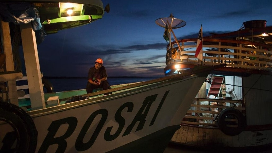 "In this May 22, 2014, photo,  a man sits on the  ""Almirante Barbosa"" during a quick stop at the port of Manacapuru, near Manaus, Brazil. Boats like the Almirante Barbosa are the lifeline of Brazil's Amazon region, where they transport passengers and staples ranging from rice to diapers, and deliver them to remote riverside villages inaccessible any other way. (AP Photo/Felipe Dana)"