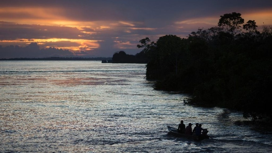 In this May 22, 2014, photo, a small boat navigates on the Solimoes river near Manaus, Brazil. While most tourists opt for speedboats for their jungle journeys, a riverboat day trip can give even Cup visitors on a tight schedule a taste of authentic Amazonian life. (AP Photo/Felipe Dana)