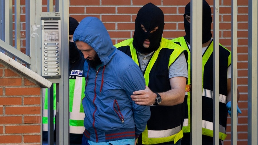 MADRID, SPAIN - JUNE 16:  Spanish policemen arrest a man suspected of belonging to an international Jihadist recruiting network at Rutilo street on June 16, 2014 in Madrid, Spain. Spanish Police this morning made eight arrests in raids against an Islamist cell believed to be recruiting Jihadists to fight in Syria and Iraq for ISIL (Islamic State in Iraq and the Levant) Terrorist Group.  (Photo by Gonzalo Arroyo Moreno/Getty Images)
