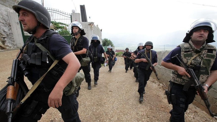 Albanian police enter the lawless village of Lazarat, 230 kilometers (140 miles) south of capital Tirana, wendesday, June 18, 2014, combing houses for drugs. Near-continuous gunfire rings out from the lawless village as hundreds police still battle well-armed marijuana growers trying to thwart a government crackdown. (AP Photo/Hektor Pustina)