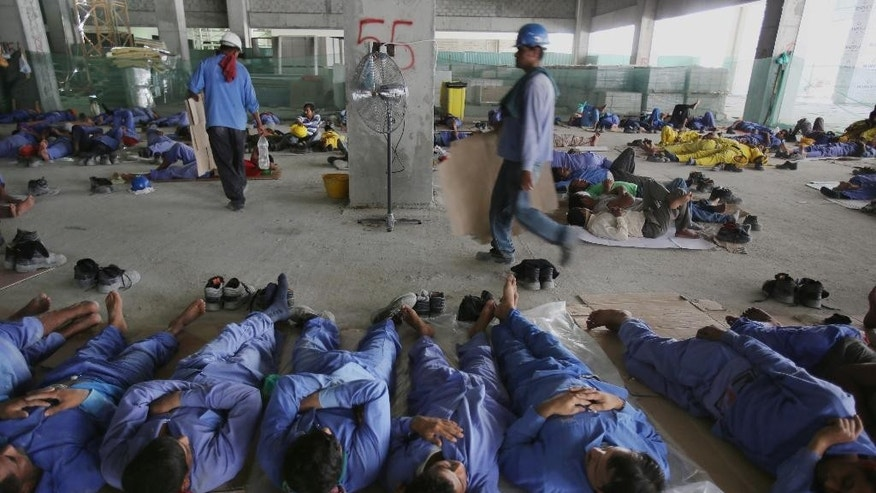 In this Sunday, June 15, 2014 photo, laborers nap on pieces of empty cardboard boxes during their midday break at the Dragon Mart Phase 2 construction site in Dubai, United Arab Emirates. A midday work ban goes into effect across the United Arab Emirates for construction workers and outdoor laborers, on Sunday, to protect them from the risks of direct sunlight and extremely high temperatures during the hottest summer months. (AP Photo/Kamran Jebreili)
