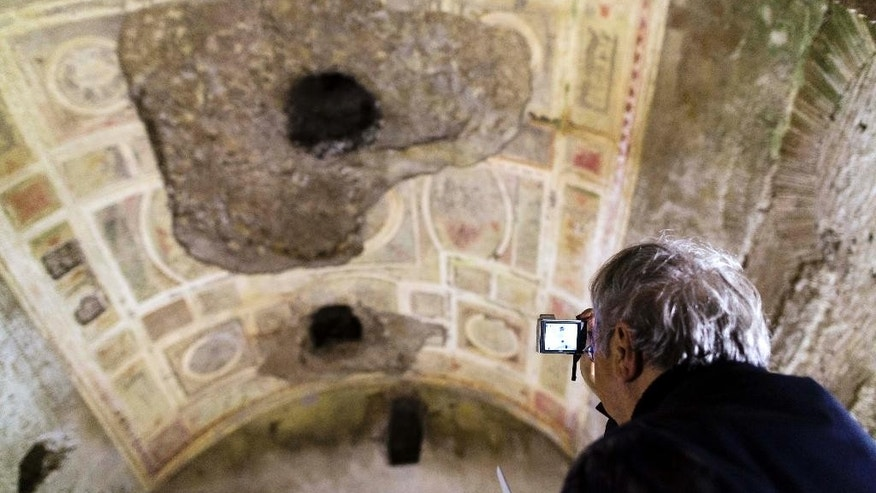 A journalist scans the frescoed ceilings of a room during a visit organized for the media of the Roman Emperor Nero's Golden Palace 'Domus Aurea' in Rome, Wednesday, June 18, 2014.  Archaeologists and restorations experts said Wednesday that research, including digital simulation aimed at solving the Domus Aurea's chronic humidity problem, has indicated that trees in a park on the Oppian Hill hurt the palace's stability. The nearly 2,000-year-old structure was closed to visitors in 2010, after decades of stability problem. Tree roots and rainwater sink into the walls, damaging frescoes and causing parts of the ceiling to fall off. (AP Photo/Domenico Stinellis)